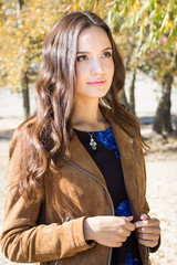 Young beautiful brunette woman in park, outdoor autumn portrait