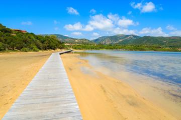 Wooden walkway to Chia beach along a salt lake, Sardinia island