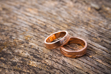 Pair of rose-gold wedding rings on wooded background