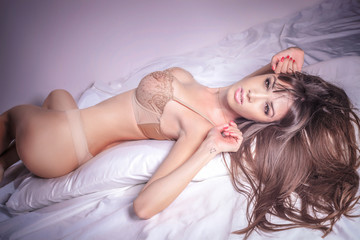 Attractive brunette woman posing in bed