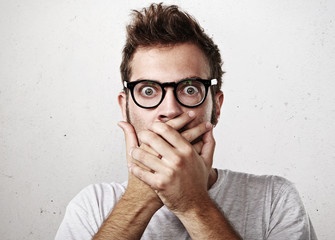 Portrait of a shocked young man covering his mouth with hands