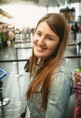 portrait of smiling brunette woman standing at queue in airport