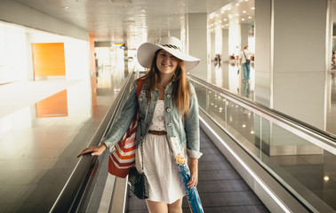 portrait of smiling woman wearing hat in airport at escalator