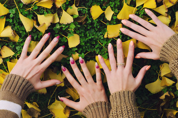 Female hands touching ground on beautiful autumn day