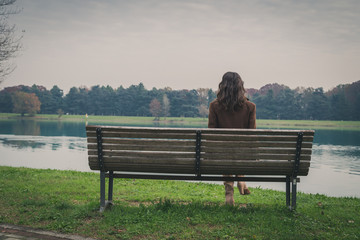 Beautiful young woman sitting on a bench in a city park