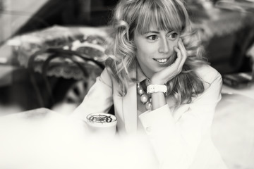 Black and white portrait of young woman sitting in cafe