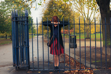 Sad woman leaning on gate in park