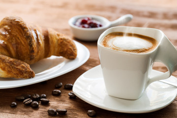 Creamy cup of coffee with croissant in background.