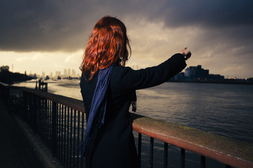 Woman admiring sunset over river in city