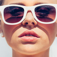 Beautiful young female face with sunglasses