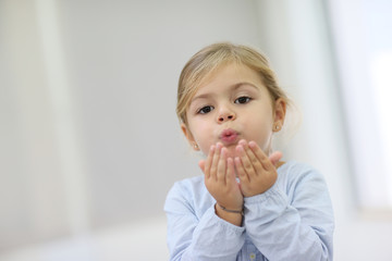 Cute little girl blowing kisses away