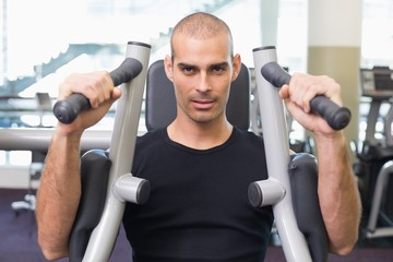 Serious man working on fitness machine at gym