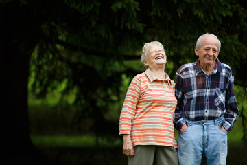 Happy senior couple looking at camera and laughing