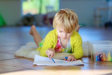 Little girl drawing at home lying on the floor