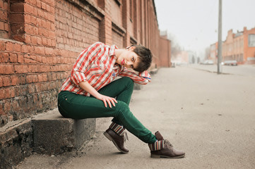 Woman wearing checkered shirt and jeans. Short hair