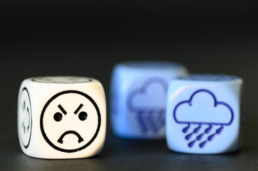 concept of sad rainy weather - emoticon and weather dice on blac