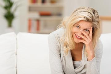 moderne ältere frau stützt lächelnd den kopf auf