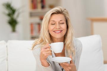 frau mit geschlossenen augen genießt eine tasse kaffee