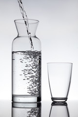 empty glass and a carafe filled with water
