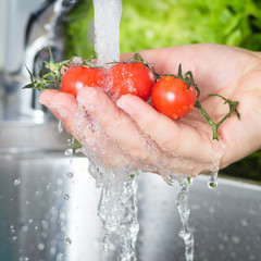 Washing grape tomatoes under running water