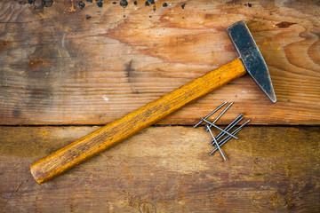 Hammer and nails on wooded background, top view