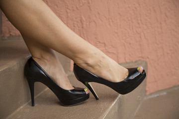 Woman's legs on stairs wearing black high heels.