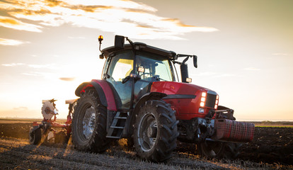 Wall Mural - Farmer plowing stubble field with red tractor at sunset