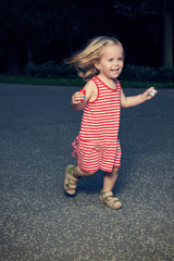 Little Blond Girl Enjoying Playing Outside in the Summer