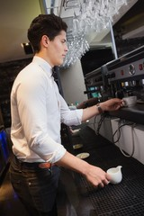 Handsome barista making a cup of coffee