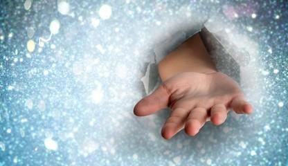 Composite image of hand bursting through paper