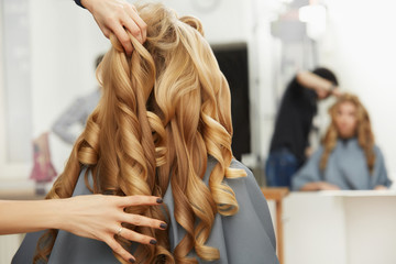 Blonde curly hair. Hairdresser doing hairstyle for young woman i