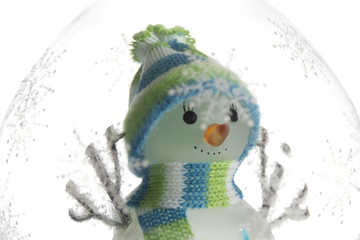 Toy snowman in a glass decorated with snowflakes