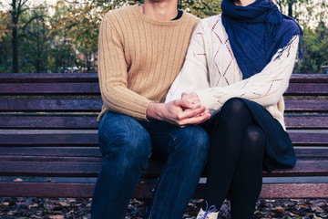 Young couple sitting on park bench