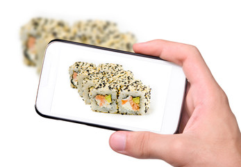 Hands taking photo fresh japanese sushi rolls with smartphone