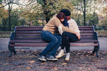 Sad young couple on park bench
