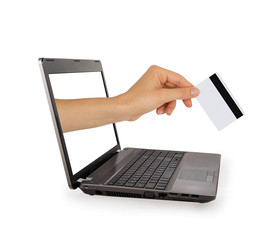 Hand with credit card comes from laptop screen