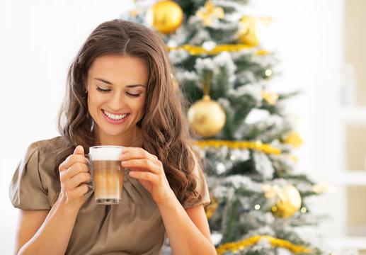 Portrait of happy young woman drinking latte macchiato