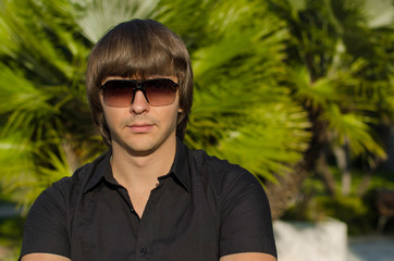 Young handsome man in sunglasses posing over palms on the beach.