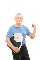 Happy senior with gripped fist holding a weight scale