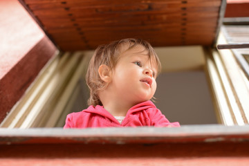 Little toddler girl looks out of the window
