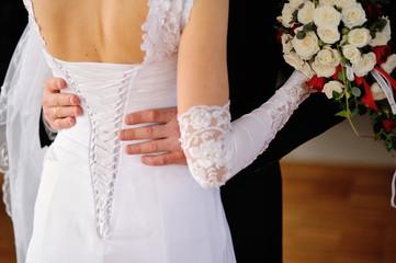 groom embraces the bride, bride corset