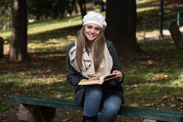 Attractive Woman Reads The Book In Autumn Forest