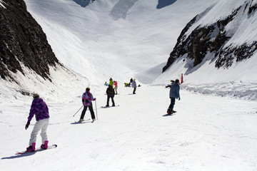 Skiers and snowboarders going down the slope.