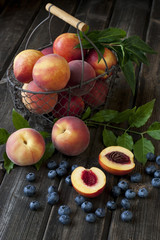 Colorful summer fruits - nectarines and peaches on wooden table