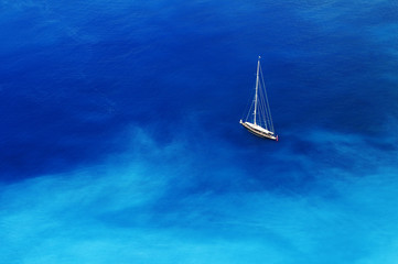Sailing boat in turquoise blue water.
