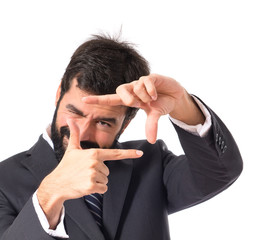 Businessman focusing with his fingers on a white background