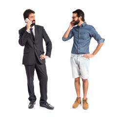 Twins talking to mobile over white background