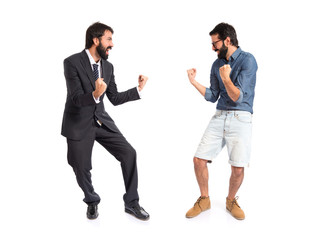 Twin brothers doing victory gesture over white background