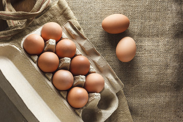 Eggs in paper pack on wooden table top view