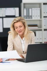 geschäftsfrau im büro schaut auf unterlagen